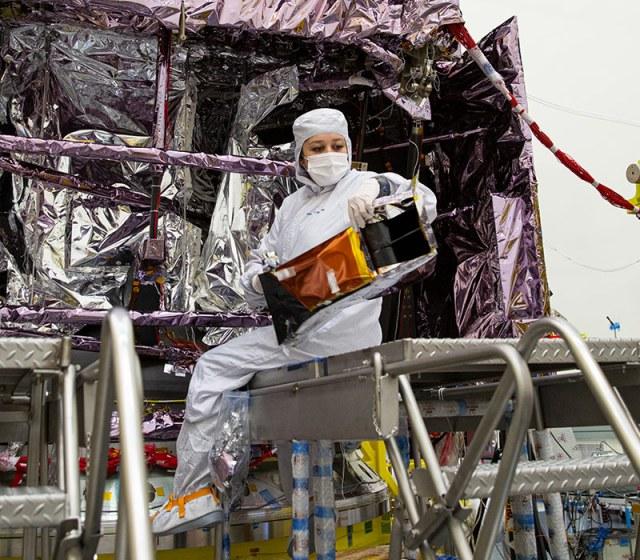 Female worker on ladder near spacecraft