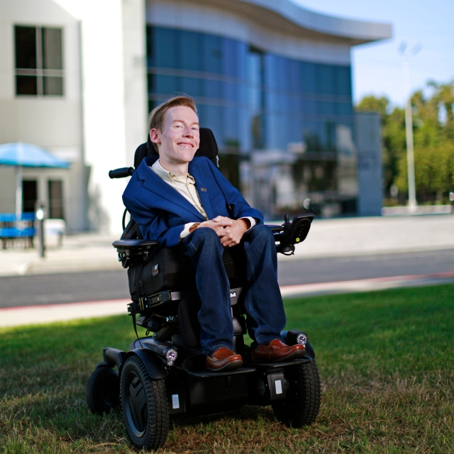 A white male in a wheel chair dressed in a blue suit