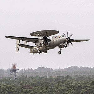 E-2D aircraft on takeoff over forrest