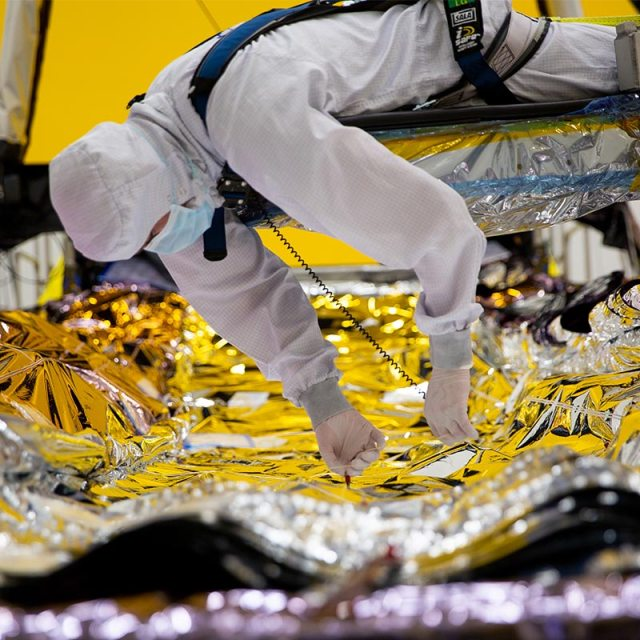 man in bunnysuit working on JWST sunshield