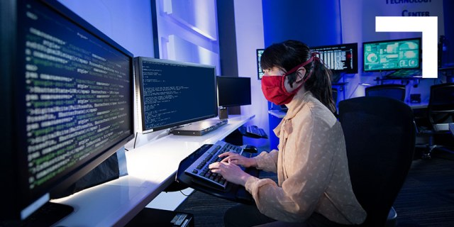 Woman wearing mask working on a computer