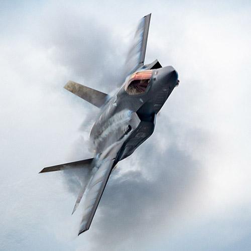 F-35 fighter jet bursting through clouds