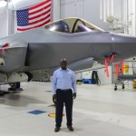 Black man stands smiling in front of aircraft