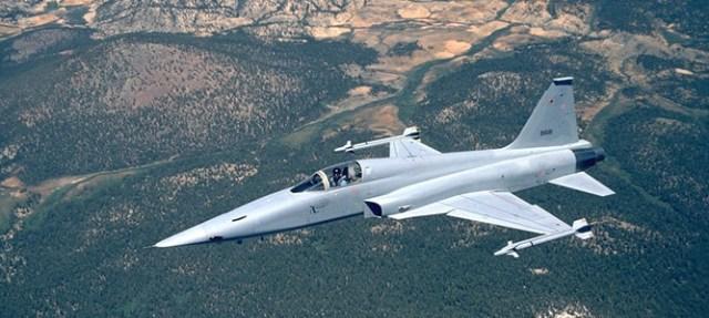 F-5 Tiger Fighter Jet flying over mountain range