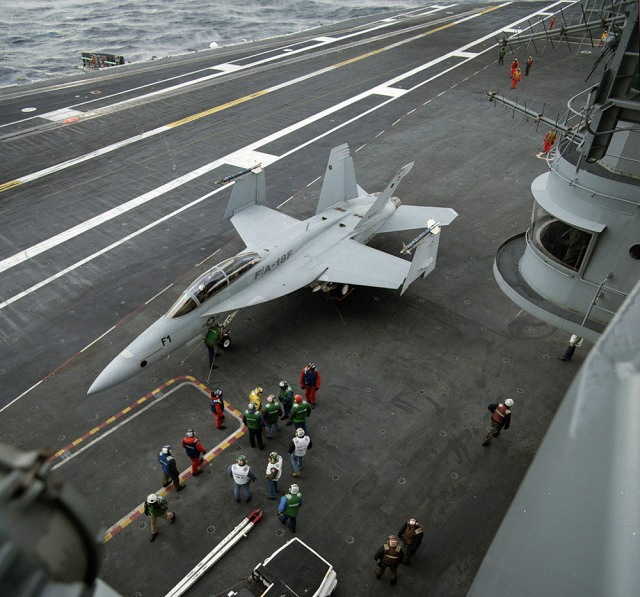 FA-18 stationed aircraft carrier deck with several personell around it