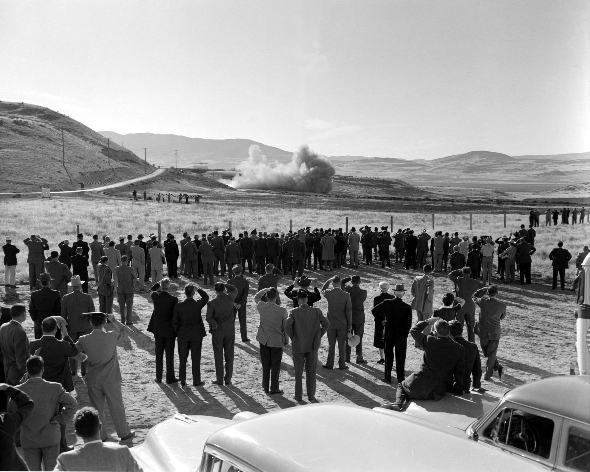 people watching rocket motor test in desert