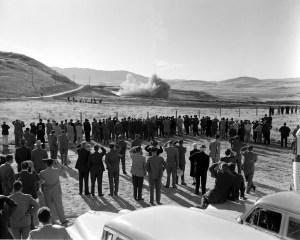 people watching rocket motor test in desert