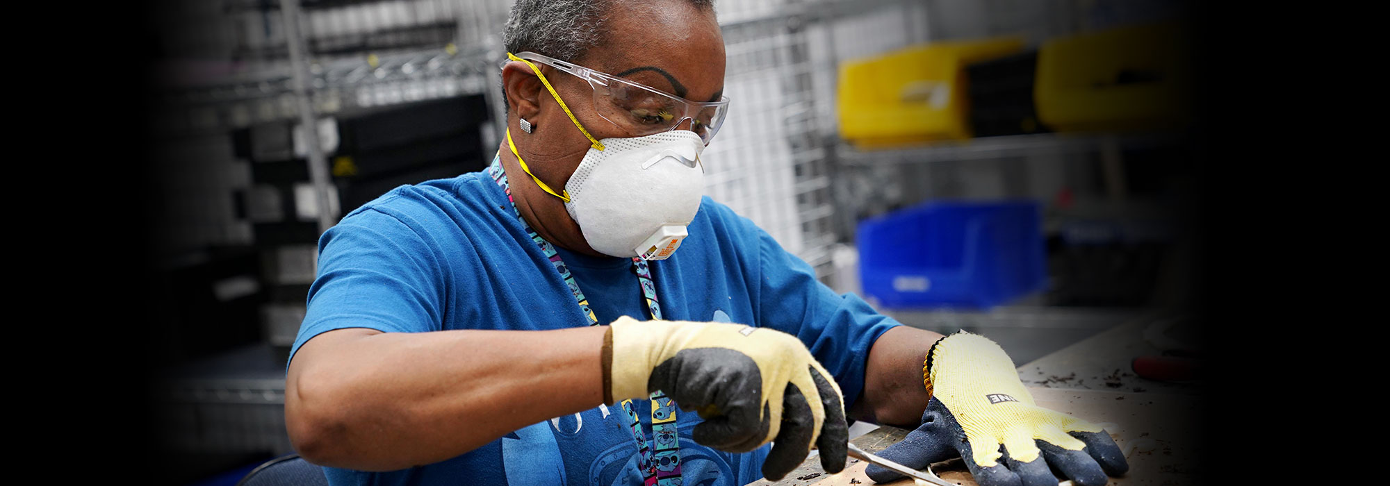 African American woman wearing work gloves and an N95 mask