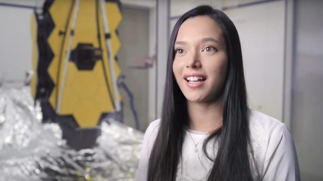 white female smiling in front of space telescope