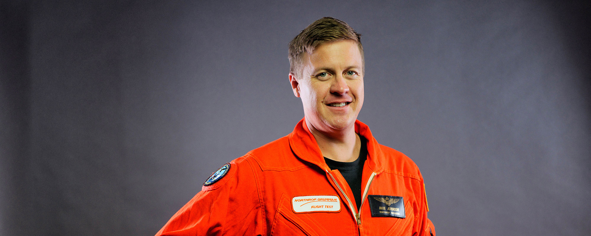 Headshot of man in orange flight suit