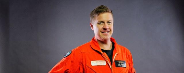 Headshot of man in orange flight suit