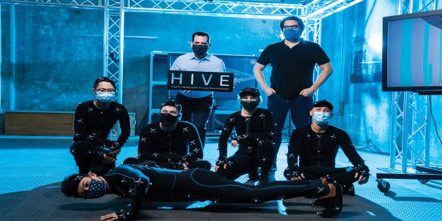 Seven engineers pose for a picture in a blue lit room. Five of them are in black jump suits.