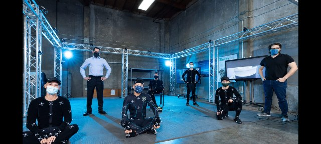 a group of five people wearing black body suits with motion tracking infrared sensors