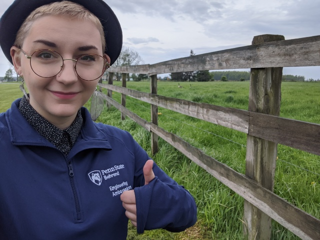 white female intern standing next to wood fence in green field