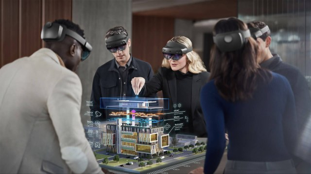 a group of people wearing HoloLens VR headsets stand around a digital image