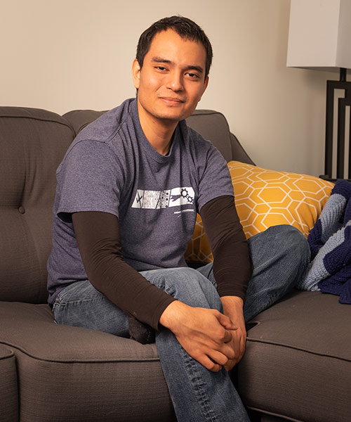 man smiling while sitting on couch