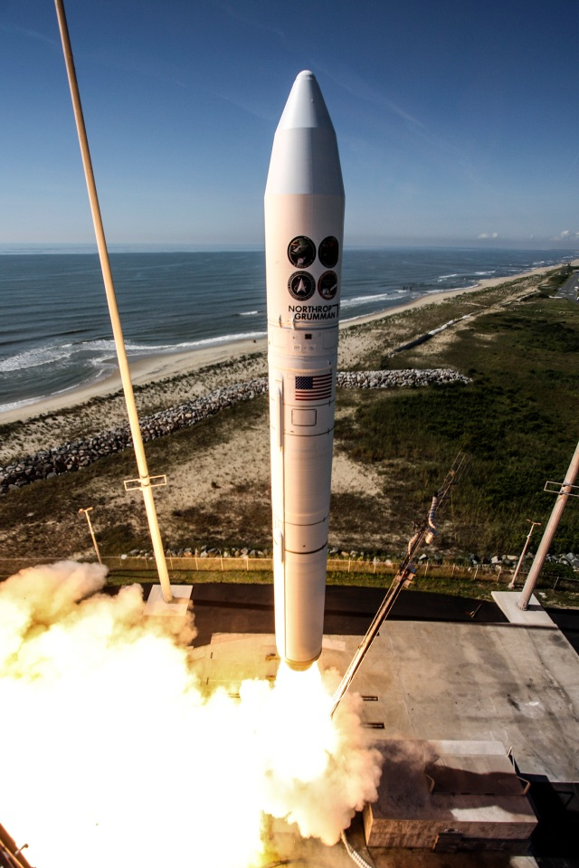 A rocket launching from shore of Wallops Island, Virginia in from of blue sky and blue ocean.