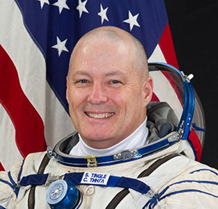 Bald man wearing astronaut uniform in front of American Flag