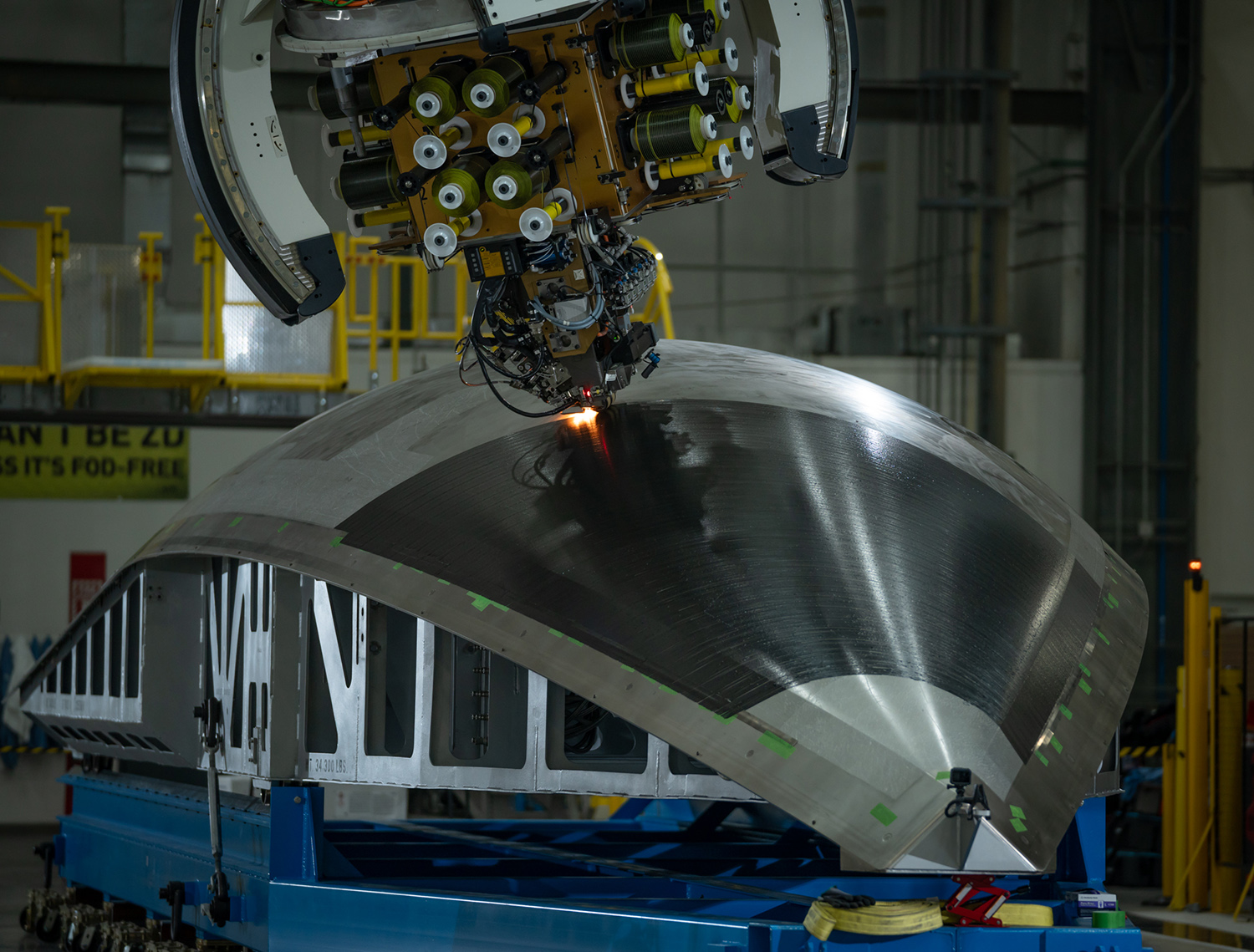 Northrop Grumman's dockable gantry system places the first layer of composite fiber on OmegA's first fairing petal structure. (March 2020)