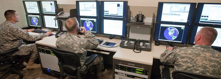 Three men in military camo uniforms looking at multiple computer screens.