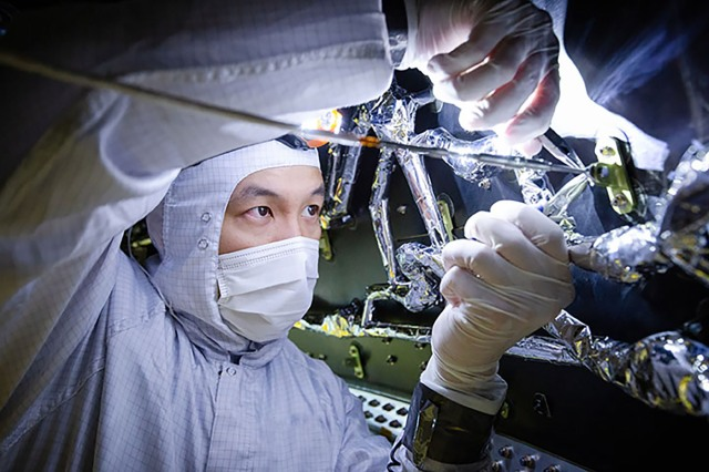 Asian man works on large part of space telescope