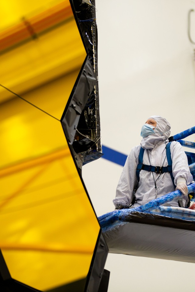 White female technician completes an operation on a space telescope