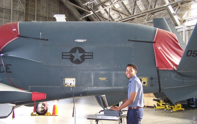 Young African American Male working on computer with Global Hawk in background