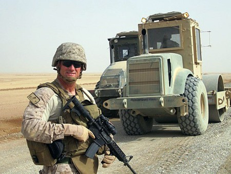 US Marine in uniform holding rifle with two military trucks in background