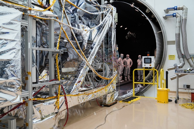 A satellite and engineers in a thermal vacumm testing facility