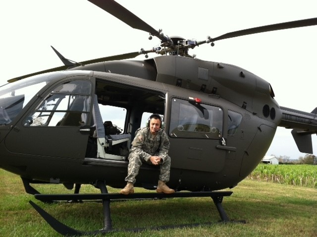 Man in military uniform sitting in open door of helicopter on ground