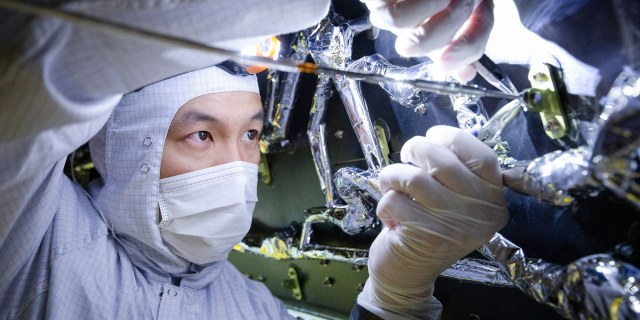 Man in cleanroom suit working on spacecraft