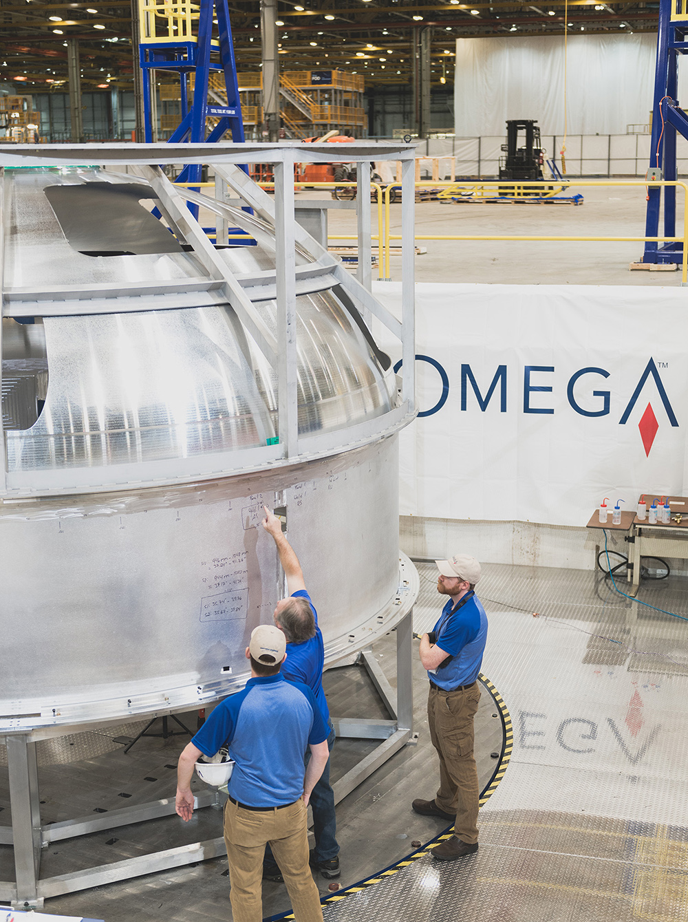 OmegA team members inspect a circumferential weld on the hydrogen tank pathfinder for OmegA's liquid upper stage. (November 2019)