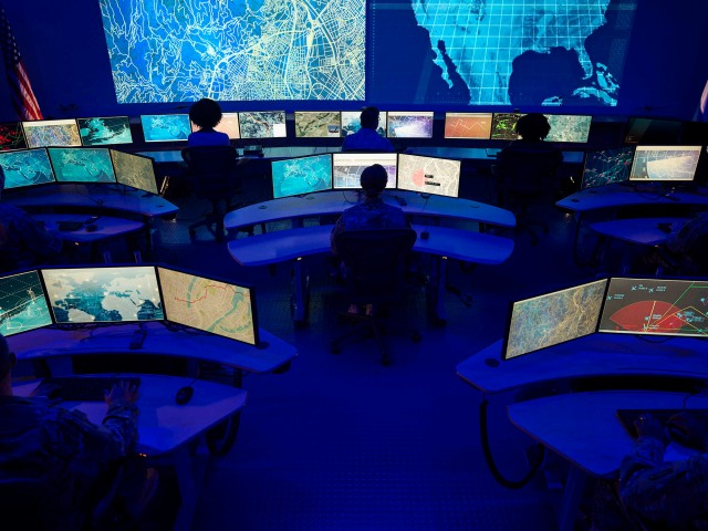 Large command center with multiple computer screens and people monitoring data.