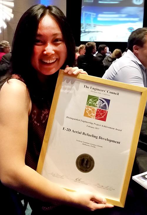 Asian woman holding engineering award