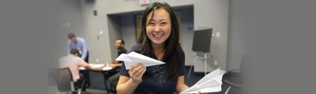 Asian woman smiling holding paper airplane