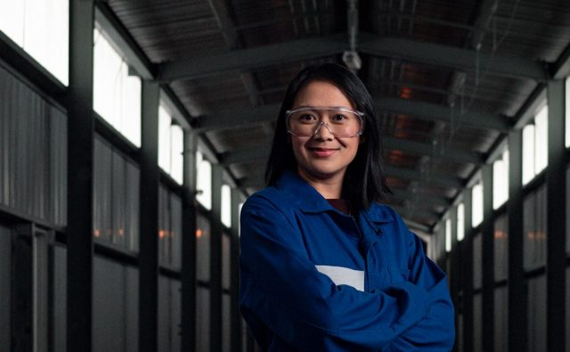 Asian female in blue lab coat and safety goggles stands in hallway of manufacturing plant