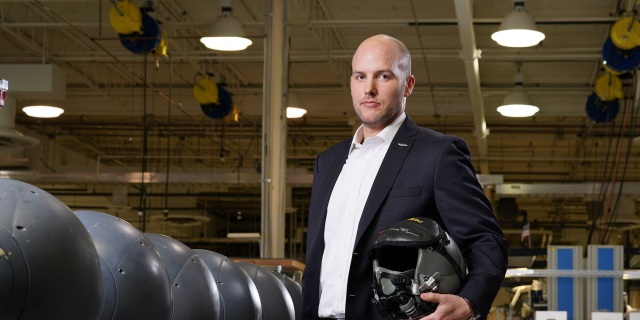 White male holds helmet while standing in manufacturing setting