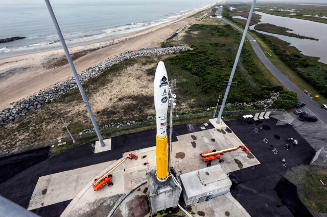 A rocket on launch pad in from of a sandy beach and ocen