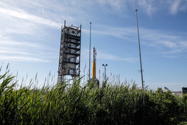 A rocket on a launch pad in front of a blue, light cloudy sky