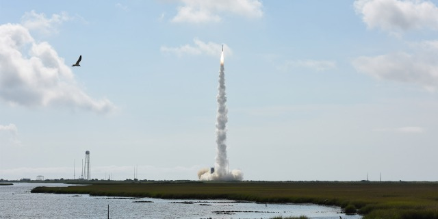 A rocket launching into space in front of a ocean