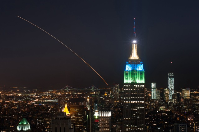 A rocket streak across the sky in New York City in front of the empire state building