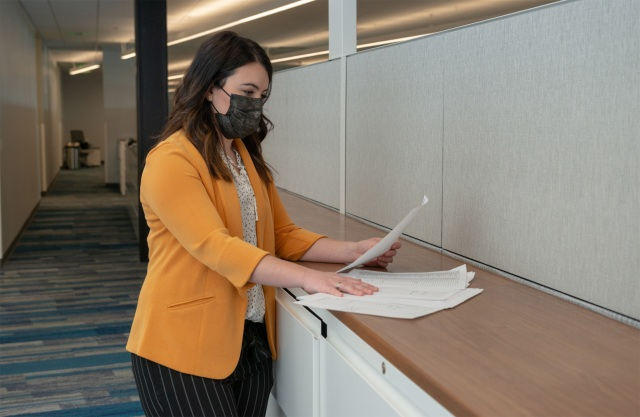A white woman with a face mask and wearing yellow inside of an office building is standing and looking at papers on a desk