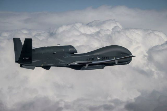 Unmanned military aircraft flying against clouds