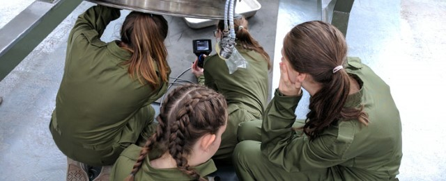 Three female STAAR students repairing an aircraft engine