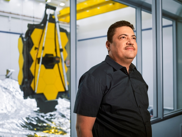 Hispanic man standing in front of James Webb Space Telescope