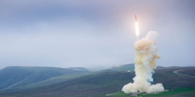 A white missile interceptor launches in front of foggy sky