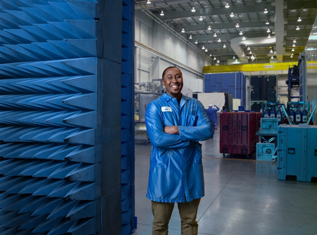 Young Black man in blue lab coat smiles with arms crossed in facility
