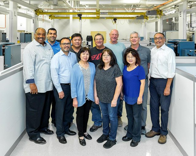 Eleven male and female team members pose in building