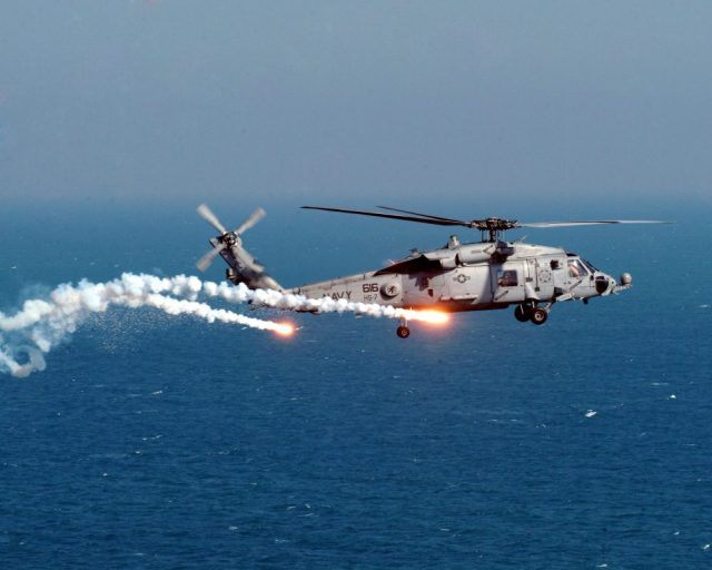 Navy helicopter dropping flares in the sky