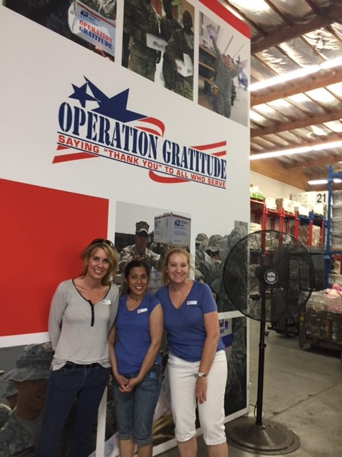 Three females posed by Operation Gratitude wall sign